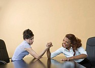 Two business women arm wrestling, indoors