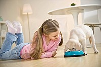 Girl 10-11 lying on floor watching puppy dog eating from bowl