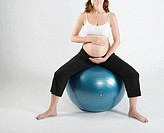 Pregnant woman sitting on exercise ball, studio shot, low section