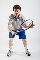 Man playing tennis, studio shot, portrait