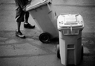 A worker wheels out a recycling bin