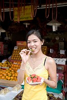 Thailand, Chiang Mai, young woman eating strawberries at outdoor market