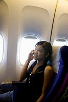 Woman talking on mobile phone in airplane cabin