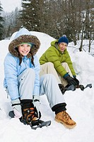 Young couple tying snow shoes near forest, portrait
