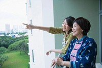 Side profile of a senior woman standing in a balcony with her granddaughter