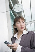 Low angle view of a businesswoman holding a mobile phone and waiting at an airport lounge