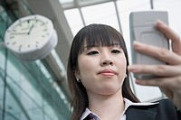 Low angle view of a businesswoman using a palmtop and waiting at an airport lounge