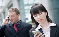 Close-up of a businesswoman using a personal data assistant with a businessman talking on a mobile phone behind her