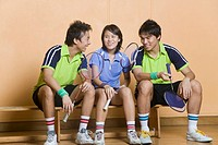 Two young men and a young woman sitting side by side on a bench and holding badminton rackets