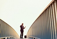 Businessman on walkway with dramatic leading graphic rails, British Columbia, Canada