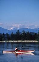 Boy paddles ocean kayak, Quadra Island, Rebecca Spit, Vancouver Island, British Columbia, Canada
