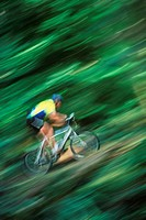 Mountain bike rider on forest trail with pan blur, British Columbia, Canada