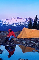 Woman camps in meadow with mountain backdrop in Whistler Alpine, Whistler, British Columbia, Canada