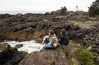 Two teens on Wild pacific trail at Ucluelet, Amphritite Point lighthouse, British Columbia, Canada