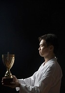 Side profile of a young man holding a trophy