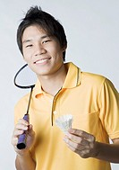 Portrait of a young man holding a badminton racket and a shuttlecock
