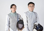 Portrait of a male and a female fencer holding fencing masks
