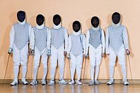 Group of people in fencing costume standing side by side