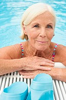 Germany, Senior woman leaning on edge of pool, portrait