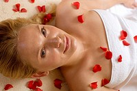Germany, woman lying on back, petals on chest