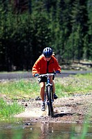 Woman Mountain Biking Into Stream