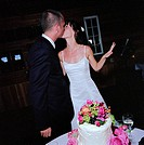 Bride and Groom Kissing with Cake