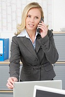 Woman in office using phone, close-up