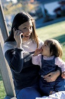 Woman Holding Baby Talking on Cell Phone