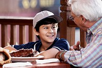 Side profile of a senior man with his grandson at a restaurant