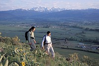 Hikers Walking Along A Grassy Ridge Overlooking A Valley