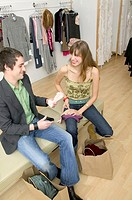 Caucasian Girl Sitting In A Trendy Boutique And Flirting With A Boy