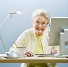 Senior woman working on computer at desk, portrait