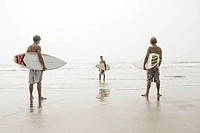 Three teenage boys 16-17 with surfboards on beach