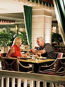 Couple holding hands having meal in restaurant