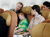 Couple looking at each other on airplane, son 6-7 sleeping