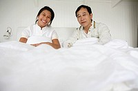 Couple in bed, smiling, portrait