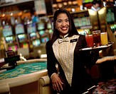 Waitress carrying tray of cocktails in casino, smiling, portrait