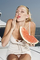 Young woman eating slice of watermelon on boat, licking finger
