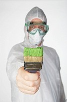 Man wearing safety mask and goggles holding paintbrush, focus on brush, portrait