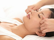 Woman lying down receiving face massage, close up