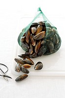 Green net bag full of mussels on chopping board