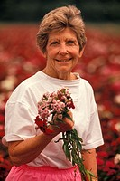 Senior woman holding flowers, portrait