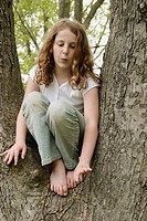 Preteen girl with wavy gold-brown hair anad freckles, sitting in tree between two large branches, knees up, in faded geans and white short-sleeved top...