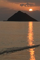 Silhouette of mountain by sea at sunrise