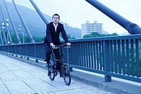 Businessman Biking on a Bridge