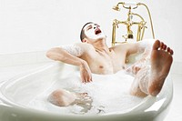 Man with Facial Mask Bathing in Foam Bath