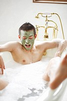 Man Relaxing in a Bathtub with a Facial Mask