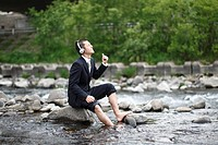 Businessman Enjoying Listening to Music at River