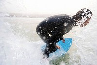 Man on surfboard splashing water