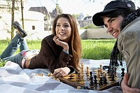 Couple playing chess in a park smiling
